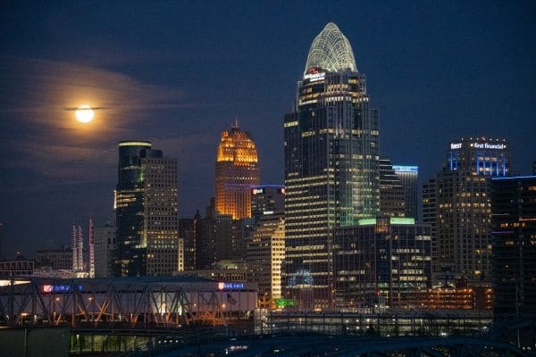 A photograph of the Cincinnati skyline taken at night with a full moon by Ryan Sciamanna.
